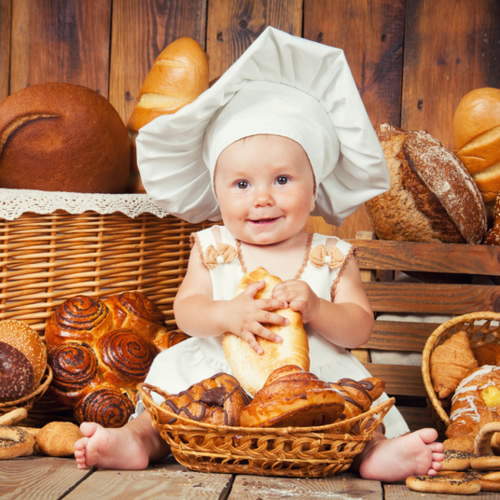 140938609 - Small child cooks a croissant in the background of baskets with rolls and bread. © Yarkovoy